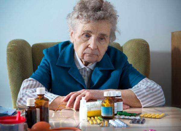 женщина сидит перед таблетками